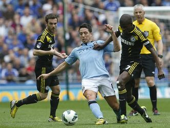 Chelsea's Ramires, right, tackles Manchester City's Samir Nasri during their English FA Cup semifinal soccer match, at Wembley Stadium in London, Sunday, April 14, 2013. (AP Photo/Sang Tan)