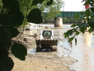 Crews remove sloppy clay from the riverbank near The Forks Tuesday afternoon.