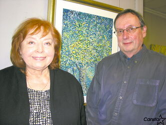 Marika Onufrijchuk Sokulski (left) and George Tanner with one of Sokulski's paintings at Medea Gallery.