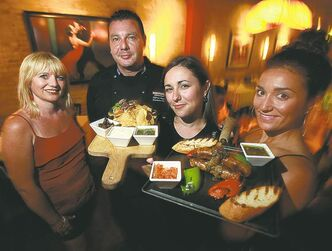 At Hermanos, from left, Monique Gillan, chef Alfonso Muary, Sara Corrigan and Anna Klassen show off their rib-eye skewers and sausage and pepper board.