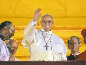 Pope Francis waves to the crowd from the central balcony of St. Peter's Basilica at the Vatican on Wednesday.