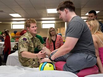 Prince Harry chats with a soldier who lost his legs.