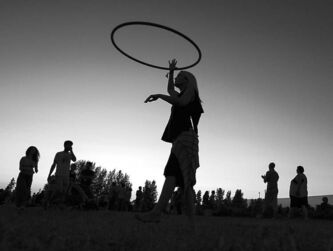 Alyx Monteith of Regina, Sask. is silhouetted against the sky at dusk while hula-hooping.