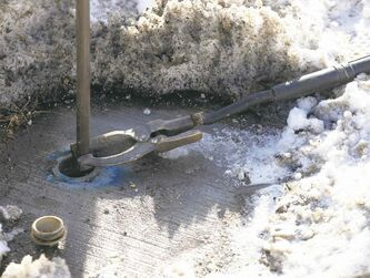Clamping electrical line  from a heavy duty battery ued by the city to a frozen water line , produces heat to thaw  frozen water line -LOCAL - A City of Wpg crew was thawing frozen water pipes on Mulvey Ave . The process uses electrical current  from a DBH battery to thaw  frozen pipe  that ran under  the street  to the  home without water . The home owner has been without water for ten days . See video Bart Kives story .  FEB. 26 2014 / KEN GIGLIOTTI / WINNIPEG FREE PRESS