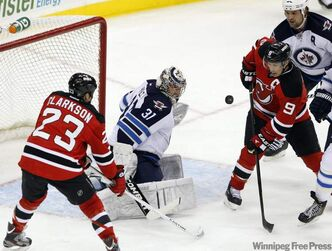 Winnipeg Jets goalie Ondrej Pavelec makes a save on a shot as New Jersey Devils' David Clarkson and Zach Parise look for the rebound during the second period of their NHL game in Newark, N.J., Tuesday.