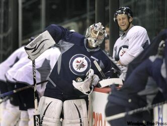 Goalie Ondrej Pavelec and defenceman Derek Meech take a breather during Friday's workout.
