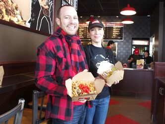Smoke's Poutinerie founder Ryan Smolkin and local franchisee Cathy Hudson are shown at the new location at 855 Regent Ave. W.