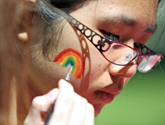 Rebecca Xie, with the Neelin High School Gay-Straight Alliance, gets a rainbow painted upon her cheek during Brandon Pride Weekend events in 2013