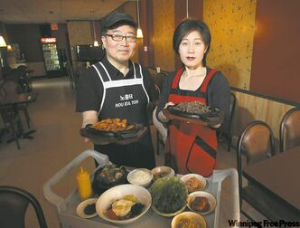 Nou Eul Tor owners Jay Yoo and wife Ju Hee Kim with a variety of dishes from their excellent menu.