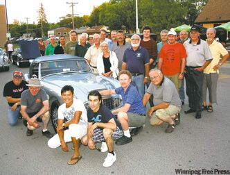 Members of the Austin Healey Club and the Triumph Drivers Club surround Roger Morcilla's 1960 Austin Healey 3000 at a recent Sunday night cruise.