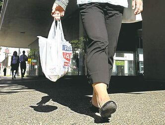 Linda Leu carries a single-use plastic carryout bag in downtown Sacramento, Calif.