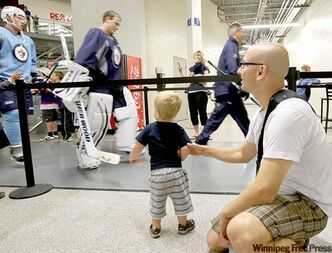 Cameron Neufeld and his son Eli watch as the players leave the ice at the Winnipeg Jets rookie practice.
