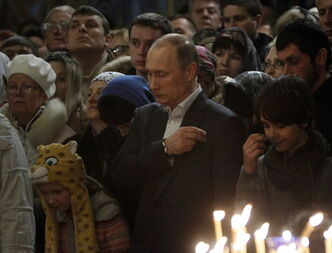 Russian President Vladimir Putin crosses himself as he attends an Orthodox Christmas service at the Holy Face of Christ the Savior Church in Sochi last January.