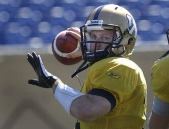 Joey Elliott tosses ball during practice Monday.