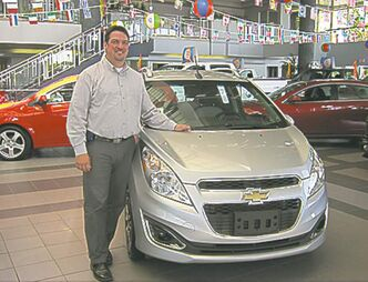 Gauthier Chev used-car manager Jim Mann Baxter with a new GM Spark.