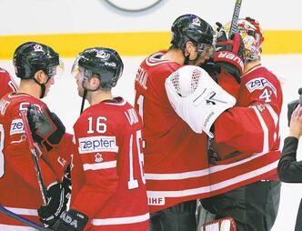 Canadian goalie Mike Smith (far right) is congratulated by teammate Jordan Staal after shutting out Sweden on Thursday.