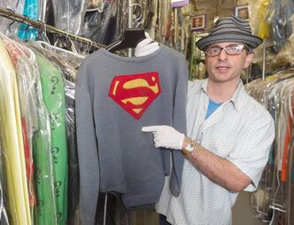 "Comisar shows off the costume  George Reeves wore in the  1950s TV show ""Adventures of  Superman."""