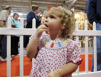 "In Nov. 29, 2013 photo taken from video, Ava Moser, 2, chews on a candy cane after visiting with ""Santa"" Cliff Snider at the Christmas Carousel show in Raleigh, N.C. The Clayton, N.C., girl asked Santa for a Barbie and princess dress-up clothes. (AP Photo/Allen G. Breed)"