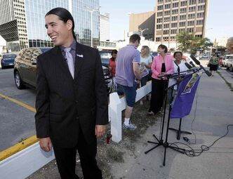 Robert-Falcon Ouellette shares a laugh with a reporter after picking up trash that turned out to be the reporter's  coffee cup before a press conference about downtown surface parking lots Friday.