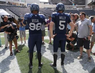Defensive lineman Jason Vega and quarterback Drew Willy model the new outfits Tuesday at Investors Group Field.