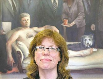 Maggie  Sutherland sits in front of her painting of Prime  Minister  Stephen Harper.