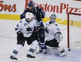 Winnipeg Jets' Blake Wheeler (26) celebrates Andrew Ladd's (16) late game tying goal against San Jose Sharks' Scott Hannan (27) and goaltender Antti Niemi (31) in third period action.