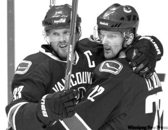 Vancouver Canucks' Daniel Sedin, right, and twin brother, Henrik Sedin