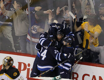 Winnipeg Jets Evander Kane, Nik Antropov, Grant Clitsome and Kyle Wellwood celebrate Kane's game-winning goal against the  Boston Bruins.