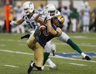 Winnipeg Blue Bombers' Julian Feoli-Gudino (83) can't hang onto the ball with pressure from Saskatchewan Roughriders' Tyron Brackenridge (41) and Samual Hurl (31) during the second half of CFL action in Winnipeg Thursday, August 7, 2014.