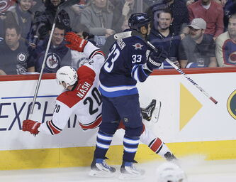 Winnipeg Jets' Dustin Byfuglien (33) dumps Carolina Hurricanes' Riley Nash (20) during first period NHL action in Winnipeg on Saturday.