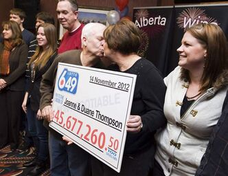 Joanne and Duane Thompson are surrounded by family members as they pose with a giant cheque presented to them in 2012 in Lethbridge, Alta. Saturday's jackpot is a record $55 million.