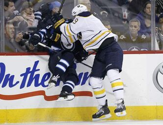 Winnipeg Jets defenceman Tobias Enstrom gets smashed into the boards by Buffalo Sabres enforcer Steve Ott during first-period NHL action at the MTS Centre in Winnipeg Tuesday.
