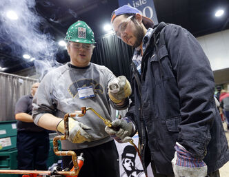 Andrew Jones (right), age 21, solders a copper pipe with Ryan Gillespie from the Piping Industry Technical College at the event Wednesday.