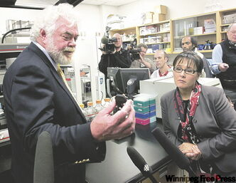 Dr. Frank Plummer, scientific director of the microbiology lab, shows federal Health Minister Leona Aglukkaq a gene chip prior to the announcement of support for five new research projects.
