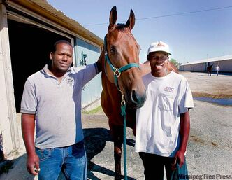 Grooms Anthony Nelson (left) and Romando Ricketts, with Quaker Shaker Tony, fill a crucial role at the Downs that few Canadians will.