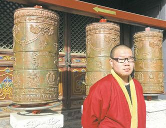 A monk next to prayer wheels at Pushou Tibetan Buddhist Temple.
