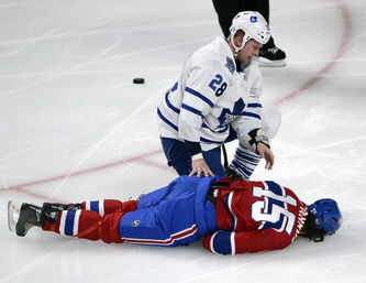 Leafs winger Colton Orr kneels over Montreal Canadiens winger George Parros after he hit his head on the ice during their fight last night.