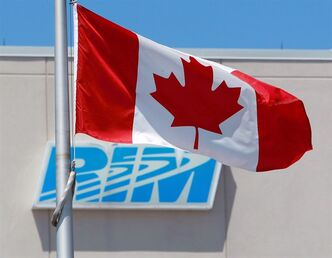 The Canadian flag flies in front of the Research In Motion (RIM) company logo on one of their buildings in Waterloo, Ont., on June 29, 2012. THE CANADIAN PRESS/Dave Chidley