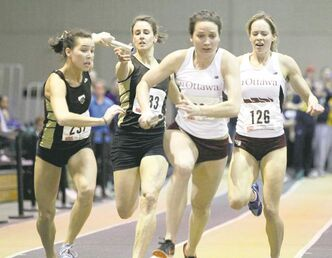 Bisons' Kim Bordun hands the baton to Michelle Lajoie (far left) in the 4x400 women's relay at the CIS track and field championships at the U of M.