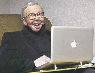 FILE - In this Jan. 12, 2011, file photo, movie critic Roger Ebert works in his office at the WTTW-TV studios in Chicago. Early Tuesday, June 21, 2011, Ebert's Facebook page was taken offline briefly after Ebert posted a message on Twitter about
