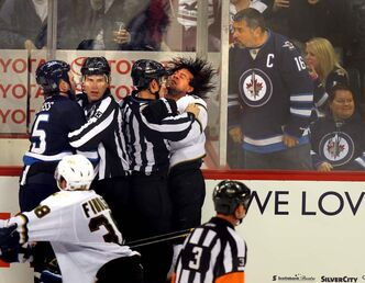 Winnipeg Jets' Tanner Glass and Dallas Stars' Adam Burish go at it despite having a pair of linesmen holding them back in a chippy third period.