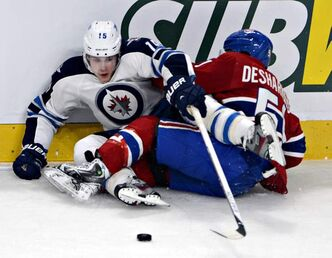 Winnipeg Jets' Mike Santorelli reaches for the puck while tangled with Montreal Canadiens' David Desharnais during second-period National Hockey League action in Montreal Thursday.