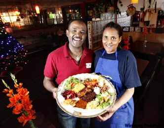 Robel Arefaine and Hamelamal Shibshi hold a mixed platter from Kokeb Restaurant on Ellice Avenue. Winnipeg restaurant-goers have been enjoying delights from East Africa since the first wave of immigrants arrived on the Prairies in the 1980s.