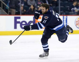 Winnipeg Jets' Andrew Ladd fires a puck during warmup before his team plays the Nashville Predators in Winnipeg on Tuesday. The entire team wore a Rick Rypien jersey during the warmup in honour of 27-year-old Rypien, who had a long history of depression and killed himself less than two months after he signed with the Jets in 2011.