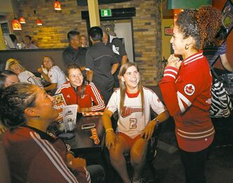 Olympic bronze medalist Desiree Scott chats with University of Winnipeg Wesmen soccer captain Stephanee Ophey (2) and her teammates on Friday.