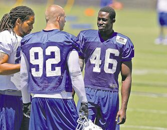 Indianapolis Colts linebacker Daniel Adongo (right) chats with linebacker Bjoern Werner (92) and tight end  Justice Cunningham during practice in Anderson, Ind., on Monday.