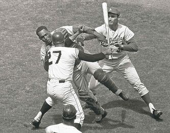 On Aug. 22, 1965 in Candlestick Park, San Francisco Giants pitcher Juan Marichal (27) swings a bat at L.A. Dodgers catcher John Roseboro as Dodgers pitcher Sandy Koufax, right, tries to break it up.