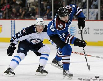 Winnipeg Jet right-winger Antti Miettinen of Finland tries to chase down Colorado Avalanche defenceman Stefan Elliot, right, as he shoots in the first period of an NHL hockey game Tuesday in Denver.