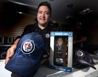 Dan Suga displays some of the Jets merchandise at a mobile Jets Gear Store in Stonewall at the Quarry Days festival site.