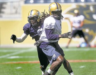 Cauchy Muamba (left) defends against Kito Poblah at practice Friday.
